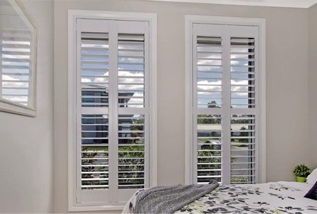 Fixed white plantation shutters are perfect for small living spaces and bathrooms.