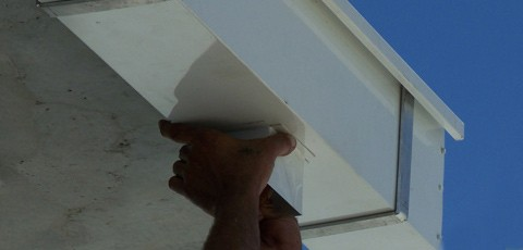 An aluminium box gutter and downpipe being assembled and installed on-site.